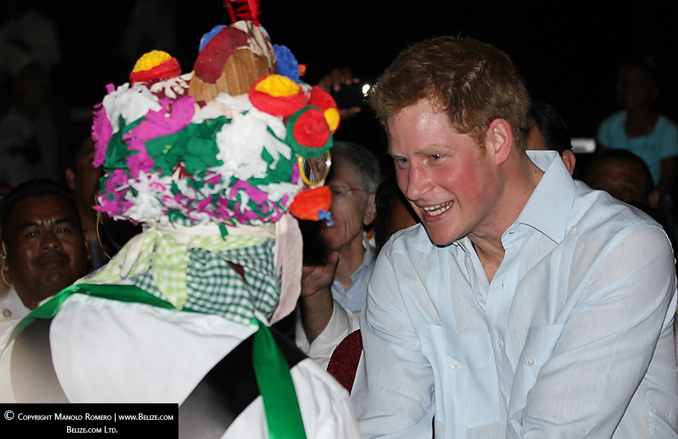 A John Canoe dancer in Belize pulls Prince Harry out to the dance floor.